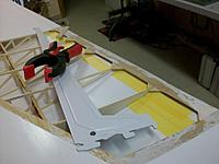 Name: wing job_4.jpg Views: 44 Size: 108.2 KB Description: Protective tape on the remaining Oratex during the insertion of the PU inpregnated balsa parts between the ribs and plywood capping (one part visible at the top). Solid iron guides ready to sandwich the trailing edge with clamps after completion
