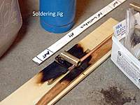 Name: solder-jigPB190233.jpg Views: 410 Size: 53.5 KB Description: Wood soldering jig worked for all 16 guns.  Probably not for many more....