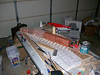 Name: spg2.jpg Views: 656 Size: 82.9 KB Description: Upper spar cap in place. Everything weighted down while glue dries. Please excuse the mess in my garage