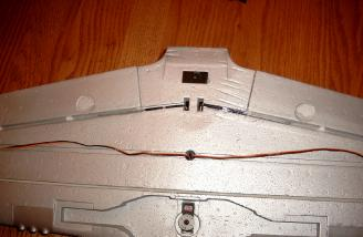 Here is a close look at the bottom of the wing that shows the retract servo and flap torque rods installed.  The aileron servo wires follow channels on the bottom of the wing before passing thru a hole to the top.