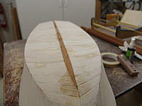 Name: DSC04470.jpg Views: 445 Size: 43.5 KB Description: The first plank is glued in position using medium CA glue and kicker spray.  Notice how the plank will run off at the turn of the stem.  This is were the plank will be trimmed and block sanded to match the sub planking of the opposite side of the hull.  T