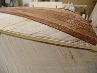 Name: DSC04475.jpg Views: 381 Size: 77.2 KB Description: Taping the basswood batten to the hull following the chine lineto the stem post.