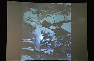 he black and white photo on the projection screen after Hoot's picture is of his mother and father in a plane. The plane belonged to his mother, his father was a pilot and that's how they met.