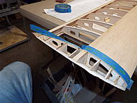 Name: DSCF8784.jpg Views: 29 Size: 1.04 MB Description: Blue tape is used to mask the wood from the sanding bar, and as a straightedge for trimming half a rib thickness from the LE sheet.