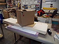 Name: DSCF8825.jpg Views: 38 Size: 1.21 MB Description: One sheet up from the bottom of that stack is the stab, pressed down while the glue holding on the sheeting cures.  Right under the box is another ply plate where the fin is pressed.  30 pounds of CDs hold it all in place and flat.
