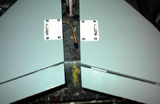 Once the servos were glued to the covers, I routed the wires through a channel I dug and screw the plates in place.