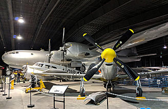 The huge B-29 overshadows a P-51 and about 4 other aircraft.
