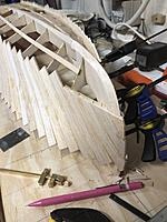 Name: IMG_2466.jpg Views: 37 Size: 3.26 MB Description: One side complete. The last boards required me to stand there using my thumbs as clamps while the CA set. Note first side overlaps the stempost as per instructions. You can also see the small scraper I've been using to remove glue lumps.