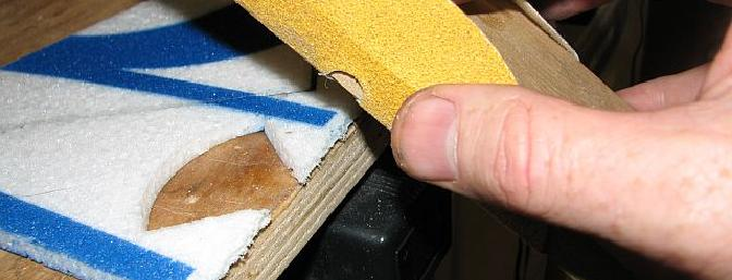 Careful use of a razor blade or Xacto knife results in a straighter edge here than sanding.