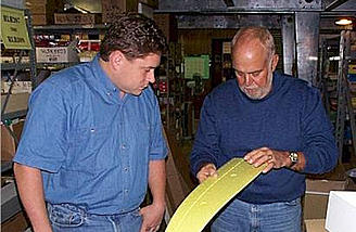 Kevin Butts and Jim Martin inspect a wing in the warehouse.