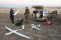 Name: Los Banos Nov09_7.jpg Views: 247 Size: 70.0 KB Description: Martin and his squadron: EMS ASW27, Renegade, Patton EPP Mini P51. Ken holding the right DUO wing. The wingo camera plane in rear.