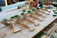 Name: AJM-3752.jpg Views: 236 Size: 79.6 KB Description: I've used 3mm (1/8) ply to make the fixtures. The flat fixtures turned out to do a great job applying down pressure on the rear edge of the ribs while being kind on the balsa.