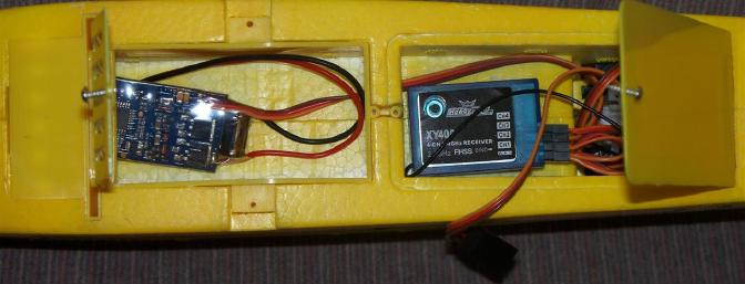 The open battery and receiver access hatches show the loose-fitting ESC and receiver.  The elevator and aileron servos are visible to the right of the receiver.  Note the tiny little retainer tab on the battery hatch which wound up breaking off despite careful handling.