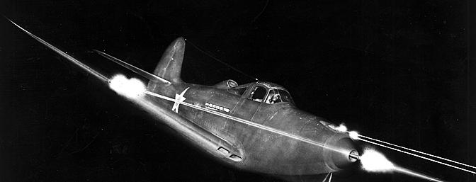 This dramatic nighttime shot of a P-39 shows all guns blazing, including the machine gun which fires through the spinner.  (Photo:  Wikimedia Commons)