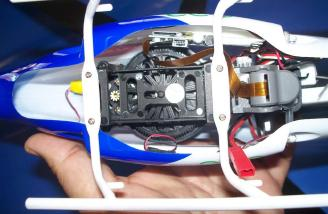This view of the underside of the Police Helicam shows the battery tray and drive gears.  The lens is the squarish gray item on the right with the gold ribbon cable.